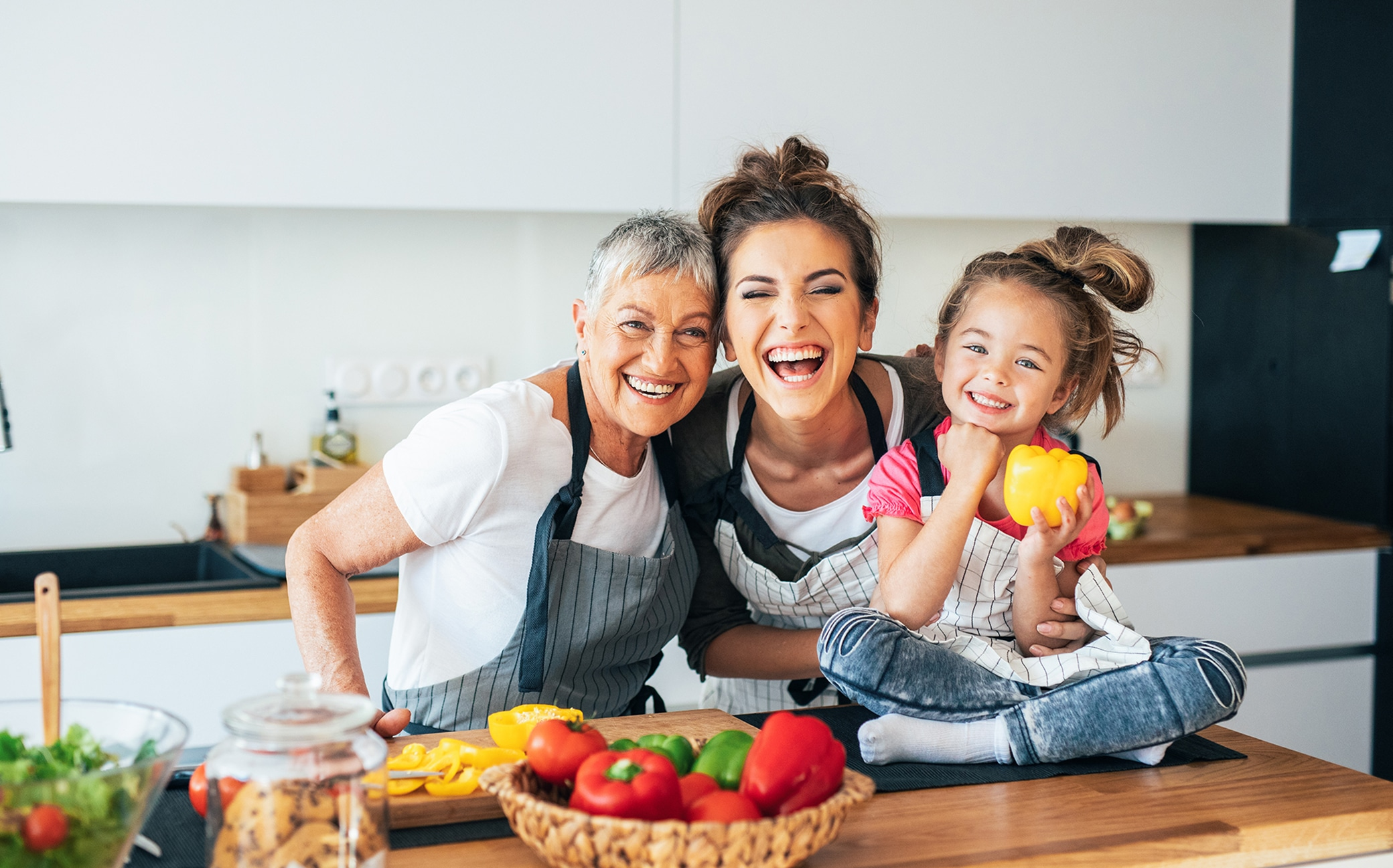 Grandmother, mother and little girl in the kitchen